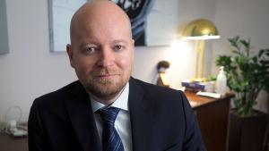 Manlig minister i mörkblå kostym i sitt arbetsrum