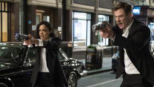 Agent M (Tessa Thompson) och Agent H (Chris Hemsworth) står med dragna vapen på gatan.