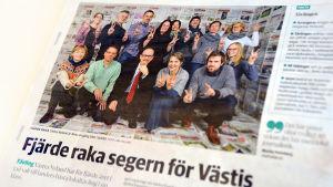 """En bild av en tidningssida där en mängd människor ser glada ut. I rubriken till artikeln står det """"Fjärde raka segern för Västis""""."""