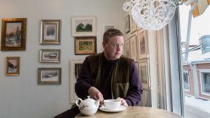 En man sitter med en vit tekopp framför sig, på bordet vit tekanna med röda blommor, mannen tittar ut genom fönstret. I bakgrunden gammaldags tavlor.