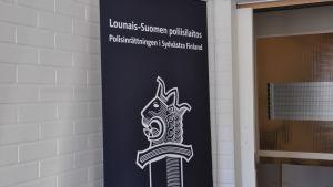 Skylt med text och polisens emblem, lejonhuvudet på svärdet.
