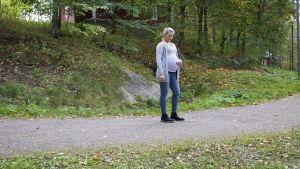 Noora seisoo ulkona tiellä ja pitää kättään vatsallaan, joka on kahdeksannen raskauskuukauden kokoinen.