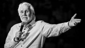 """Kenny Rogers står på scen med en mikrofon i ena handen och andra armen utsträckt. Bilden är tagen i Austin, Texas under hans """"Farewell Tour"""" den 19 mars 2017."""