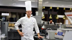 Samuel Mikander står med full kockmundering i ett restaurangkök.