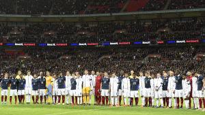 Frankrikes och Englands fotbollstrupper stod sida vid sida inför avspark i landskampen på Wembley.