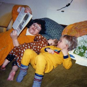 Isoäiti ja kaksi lastenlasta sängyllä maaten viettävät lukuhetkeä