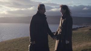 Reynolds Woodcock (Daniel Day-Lewis) och Alma (Vicky Krieps) står och håller varandra i handen vid en hög sluttning ner mot havet.