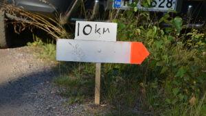 en skylt där det står 10 kilometer och en pil åt höger