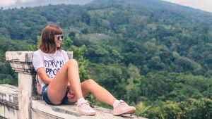 Nuori nainen istuu muurilla ja katsoo vuoristomaisemaa.