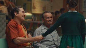 Frank Sheeran (Robert de Niro) håller sin unga dotter Peggys hand, medan Russel Bufalino (Joe Pesci) ser på dem och ler.