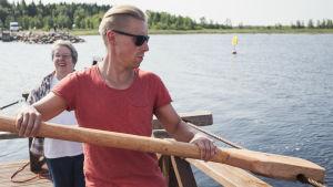 Toimittaja Nicke Aldén kuljettamassa kapulalossia Varjakansaaressa Oulussa, kesäilta, taustalla meri.