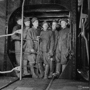 Kaivosmiehet menossa hissillä alas kaivokseen.