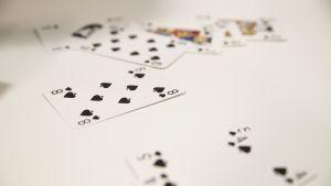Pöydällä on levällään pelikortteja, tarkemmin sanottuna pelkkiä patoja.