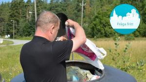 En man lyfter upp locket på en avfallscontainer
