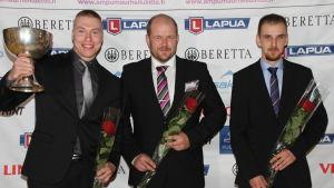 Tomi-Pekka Heikkilä, Krister Holmberg och Heikki Lähdekorpi står iklädda kostym. De håller i rosor och Heikkilä håller i en stor pokal.