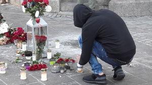 En person i munkjacka sitter på huk och tänder ett ljus vid skottplatsen.