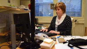 Ann-Marie Kinos sitter vid sitt arbetsbord framför datorn.
