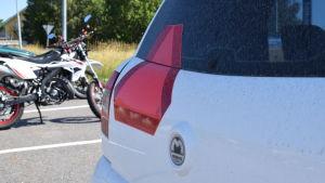 Baksidan av en mopedbil, mopeder i bakgrunden.