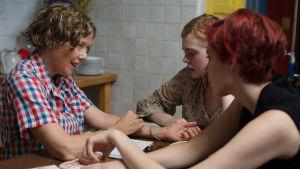Kolme naista keskustelee pöydän ääressä. Kuva elokuvasta Vuosisadan naiset.