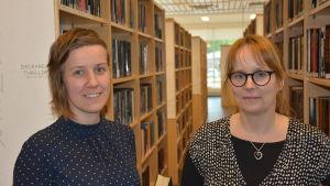 Jolanda Raitio och Karolina Zilliacus står mellan böcker i ett bibliotek.