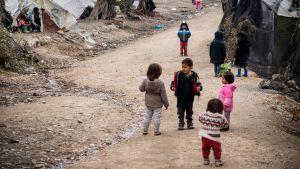 Några barn står i en grupp på ett flyktingläger i Grekland.
