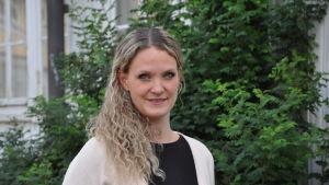 Närbild på Mikaela Sundqvist, utomhus vid en grön buske.