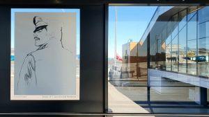 En bild av Tom of Finland på väggen i en gångramp på flygplatsen i Tallinn.