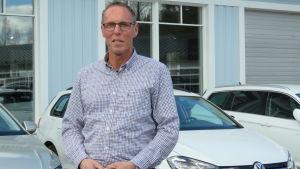 En lång man i glasögon, kortklippt hår och skjorta står utanför en bilaffär. En rad med vita bilar bakom honom.
