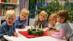 Fem barn sitter kring ett bord, i mitten på bordet en luciakrona.