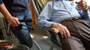 En äldre man i gungstol med en hemvårdare intill.