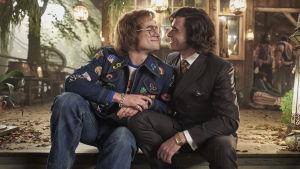 Elton John (Taron Egerton) och John Reid (Richard Madden) sitter tätt tillsammans på en trappa och ler.