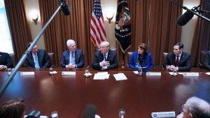 President Trump omgiven av kongressledamöter i möte runt ett stort bord, i bakgrunden USA:s flagga