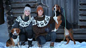 Lina och Marina i snön framför en lada tillsammans med två hundar.