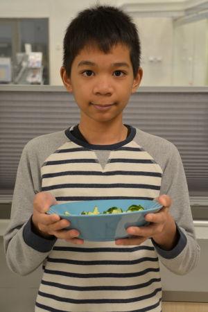 Pojke med en tallrik uppskuren gurka.