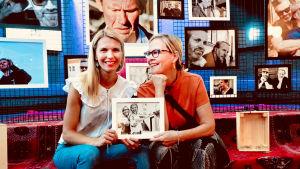 Linn Jung oh Eva Biauet sitter i fotogalleri med en bild på sig själva tillsammans i handen.