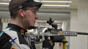 Joni Stenström skjuter med miniatyrgevär, Åbo våren 2017.