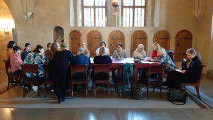 """Frivilliga i Åbo svenska församling är samlade inför högmässan för att fördela uppgifter. De sitter vid bordet som på Leonardo da Vincis tavla """"Nattvarden""""."""
