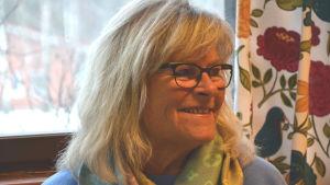 Hannele Alho, en dam med blå tröja och en färggrann scarf.