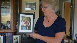 Gunborg Blom med ett fotografi av dottern Ellinor med familj som bor i Florida.