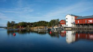 Byggnad vid vattenbrynet, brygga mad båtar och bojar.