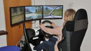 Tre dataskärmar är ihopkopplade ovanför en ratt och är placerade framför ett bilsäte. Längst nere finns pedaler.