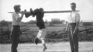 """En man leker """"flå katt"""", där han hänger upp och ner på en stång och ska ta sig framåt med att """"hoppa"""" med benen. Bilden är tagen 1930 i Jomala, Björsby, Åland."""
