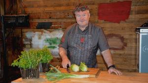 Mathias Dahlgren står med förkläde på bakom en träbänk. Framför honom ligger en kniv, gemsallad och purjolök.