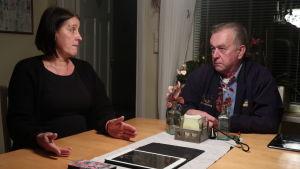 Ari Hellsberg och Beatrice Andersson sitter vid ett matbord och pratar med varandra. Utanför är det mörkt.