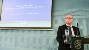 Justitie- och arbetsminister Jari Lindström i talarstol med finländsk lejonlogo.