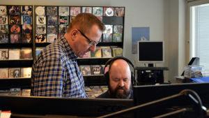 En redaktör med hörlurar och en man bredvid. Massor av musikskivor i bakgrunden.