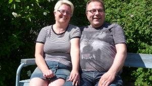 Anneli Heikkilä-Nordmyr och hennes man Mikael Nordmyr sitter på en bänk på en gård i Vasa.