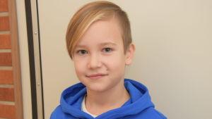 En tioårig pojke med blå munkjacka. Fotor taget inomhus mot en beige-grå vägg.