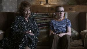 Ivy (Gemma Jones) sitter tillsammans med barnbarnet Reggie / Elton John (Kit Connor) i soffan.