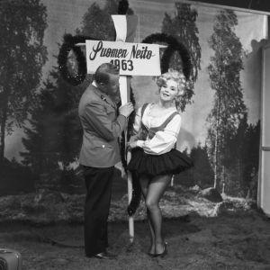 Taikuri Reijo Salminen ja näyttelijä Marjatta Kallio Iskelmäkarusellissa 1963. Kallio on pukeutunut lyhythelmaiseeen kansallispukumuunnelmaan ja kantaa Suomen Neito 1963 -kylttiä.